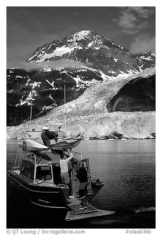 Kayakers unloading from the water taxi at Black Sand Beach. Prince William Sound, Alaska, USA (black and white)