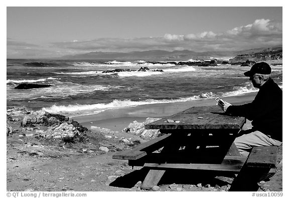Man reading on a picnic table, Bean Hollow State Beach. San Mateo County, California, USA (black and white)