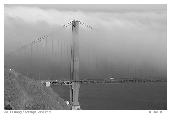 Golden Gate bridge with top covered by fog. San Francisco, California, USA (black and white)