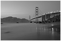 Golden Gage bridge at dusk, reflected in wet sand at East Baker Beach. San Francisco, California, USA ( black and white)