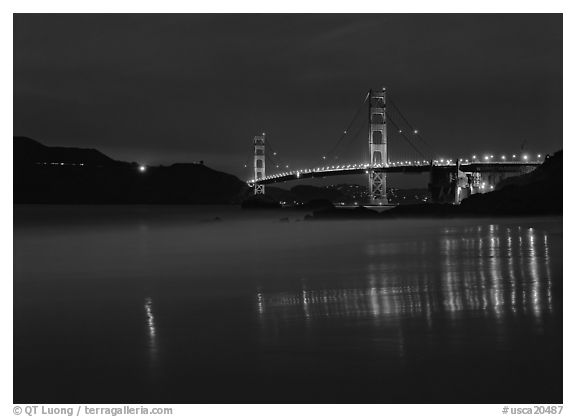 Golden Gate Bridge reflected in wet sand, blue hour. California, USA (black and white)