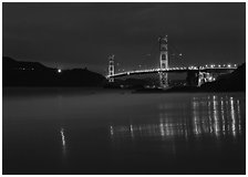 Golden Gate Bridge reflected in wet sand, blue hour. San Francisco, California, USA (black and white)