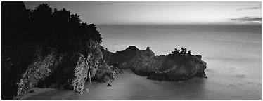 Seascape at sunset with coastal waterfall. Big Sur, California, USA (Panoramic black and white)