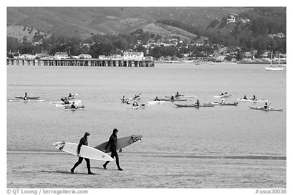 Surfers and sea kayakers, Pillar point harbor. Half Moon Bay, California, USA (black and white)