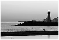 Lighthouse and Surfers in the water at sunset. Santa Cruz, California, USA (black and white)