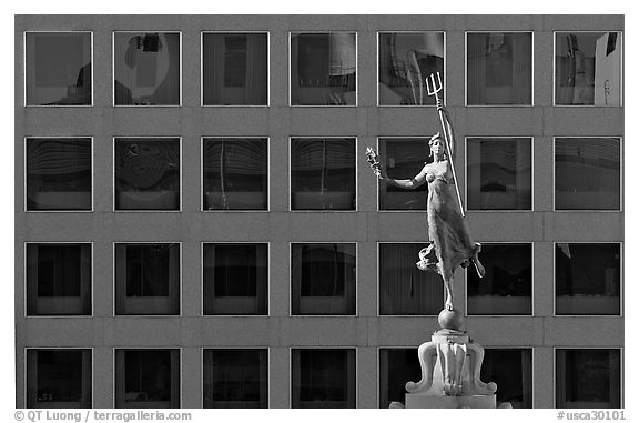 Statue on Admiral Dewey memorial column in front of modern building. San Francisco, California, USA (black and white)