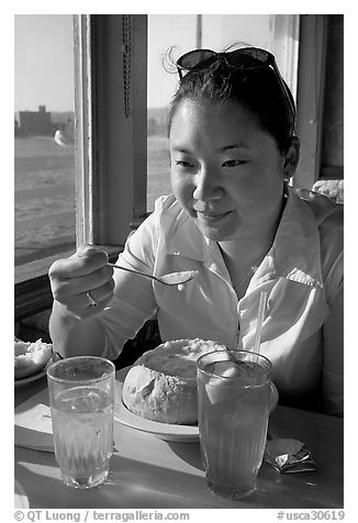 Woman eating a bown of clam chowder on the pier. Santa Cruz, California, USA (black and white)