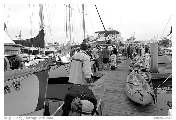 Pier with passengers preparing to board a tour boat with outdoor gear, Ventura. California, USA (black and white)