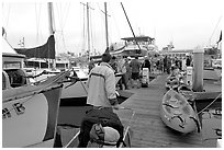 Pier with passengers preparing to board a tour boat with outdoor gear, Ventura. California, USA ( black and white)
