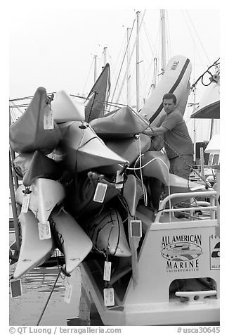 Sea Kayaks attached to a tour boat. California, USA (black and white)