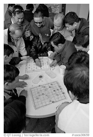 Vietnamese immigrants playing Chinese chess in a patio. San Jose, California, USA (black and white)