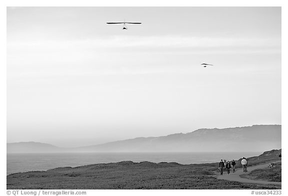 Hang gliders soaring above hikers, Fort Funston, late afternoon. San Francisco, California, USA (black and white)