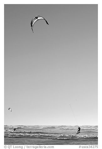 Kite surfing in Pacific Ocean waves, late afternoon. San Francisco, California, USA (black and white)