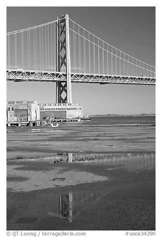 Bay Bridge reflected in water puddles. San Francisco, California, USA (black and white)