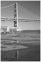 Bay Bridge reflected in water puddles. San Francisco, California, USA ( black and white)