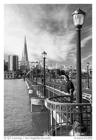 Visitor standing on pier 7, morning. San Francisco, California, USA (black and white)