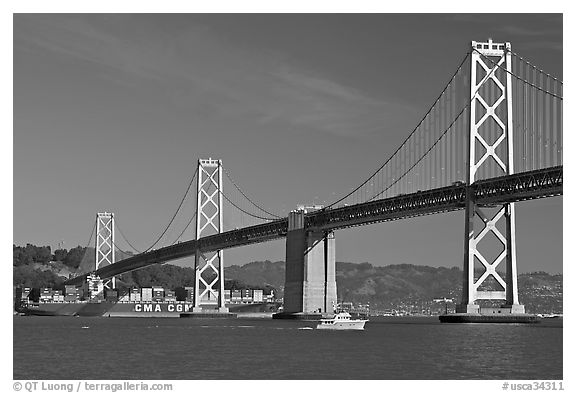 Cargo ship passing below the Bay Bridge. San Francisco, California, USA (black and white)