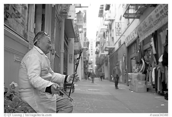 Ehru musician in Ross Alley, Chinatown. San Francisco, California, USA (black and white)