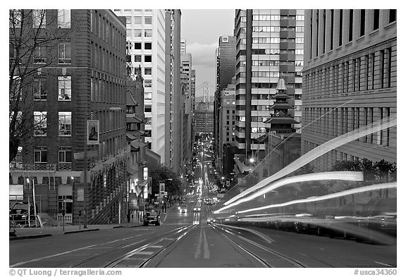 Cable-car rails,  Chinatown, Financial district, and Bay Bridge seen on California street. San Francisco, California, USA (black and white)