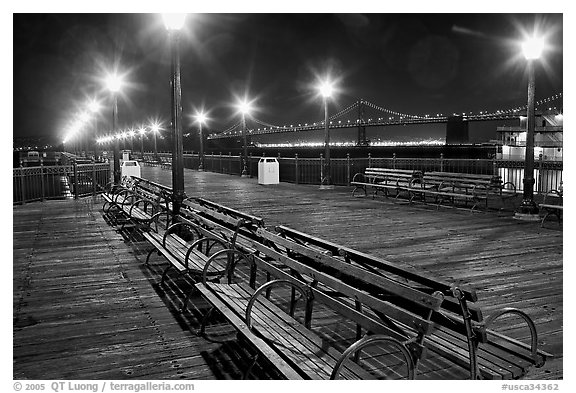 Benches and lights on Pier 7 with Bay Bridge in background, evening. San Francisco, California, USA (black and white)