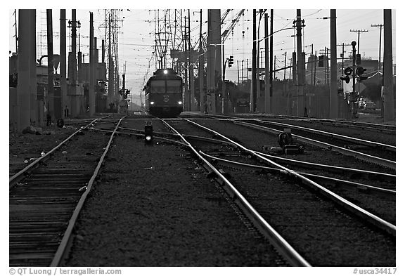 Railroad tracks, train, and power lines, sunrise. San Diego, California, USA (black and white)