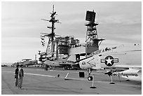 Couple looking at fighter aircraft on the Flight deck of USS Midway. San Diego, California, USA ( black and white)