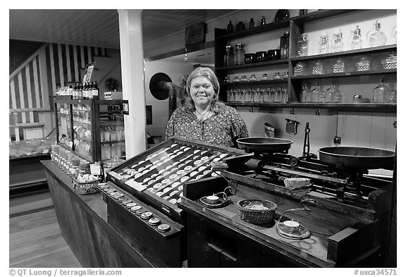 Woman standing behind counter of apothicary store, Old Town. San Diego, California, USA (black and white)