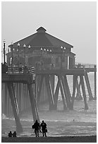 Beachgoers, surfers in waves,  and Huntington Pier. Huntington Beach, Orange County, California, USA (black and white)