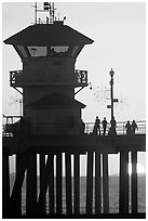 People and pier silhouetted by the setting sun. Huntington Beach, Orange County, California, USA ( black and white)