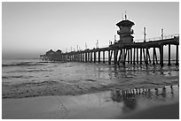 Huntington Pier reflected in wet sand at sunset. Huntington Beach, Orange County, California, USA ( black and white)