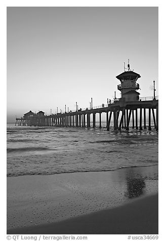 Huntington Pier and reflections in wet sand at sunset. Huntington Beach, Orange County, California, USA (black and white)