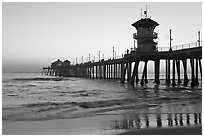 The 1853 ft Huntington Pier reflected in wet sand at sunset. Huntington Beach, Orange County, California, USA (black and white)