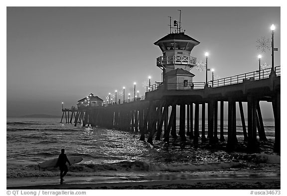 Black and white picture photo surfer and huntington pier lights at twilight huntington beach orange county california usa