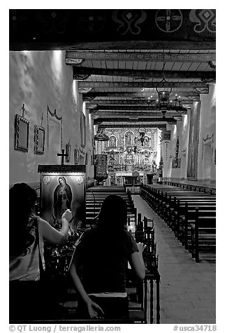 Two women light up candles in the Serra Chapel. San Juan Capistrano, Orange County, California, USA (black and white)