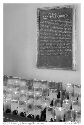 Rows of candles and sign commemorating Father Serra. San Juan Capistrano, Orange County, California, USA (black and white)
