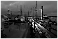 Deck and boats at night. Morro Bay, USA (black and white)