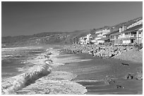 Surf and beachfront houses near Rincon Island. California, USA (black and white)