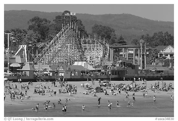 Beachgoers, and Santa Cruz boardwalk roller-coaster. Santa Cruz, California, USA (black and white)