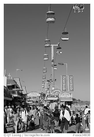 Crowd on the beach boardwalk on a summer afternoon. Santa Cruz, California, USA (black and white)