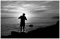 Photographer on cliffs at sunset. Santa Cruz, California, USA ( black and white)