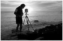 Photographer and large format camera on tripod at sunset. Santa Cruz, California, USA ( black and white)