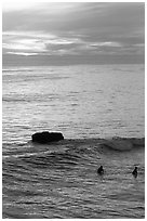 Surfers and rock at sunset. Santa Cruz, California, USA (black and white)