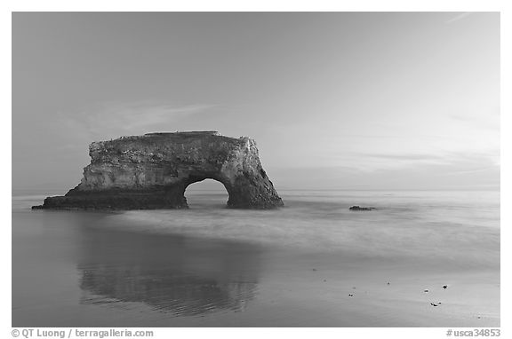 Sea arch and reflection, Natural Bridges State Park, dusk. Santa Cruz, California, USA (black and white)