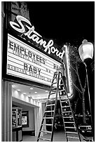 Woman on ladder arranging sign letters, Stanford Theater. Palo Alto,  California, USA (black and white)