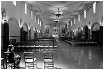 Woman sitting in chapel, Mission Santa Clara de Asis. Santa Clara,  California, USA ( black and white)