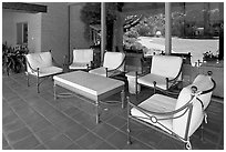 Chairs and coffee table on porch, Sunset gardens reflected. Menlo Park,  California, USA ( black and white)