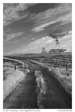 Gravel road leading to parabolic antenna, late afternoon. Stanford University, California, USA (black and white)