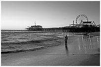 Couple reflected in wet sand at sunset, with pier and Ferris Wheel behind. Santa Monica, Los Angeles, California, USA ( black and white)