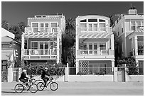 Family cycling in front of colorful beach houses. Santa Monica, Los Angeles, California, USA ( black and white)
