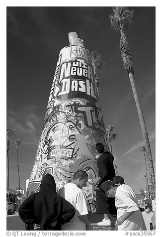 Young men decorating a cone on the beach. Venice, Los Angeles, California, USA (black and white)